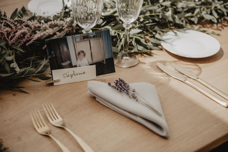Belle table en bois brut, eucalyptus et brins de lavande pour une déco de table épurée.