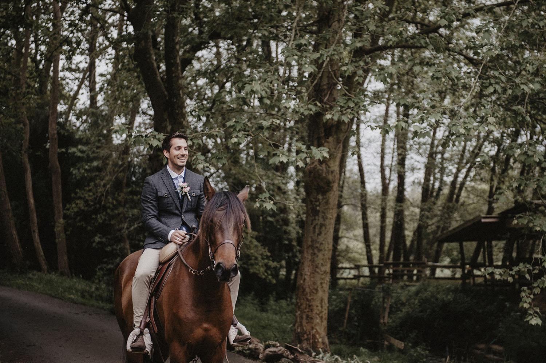 Mariage folk et rustique au Coco Barn dans les Landes, arrivée du marié à cheval à la cérémonie au bord du ruisseau. Photographe mariage lifestyle, reportage photo spontané et naturel.