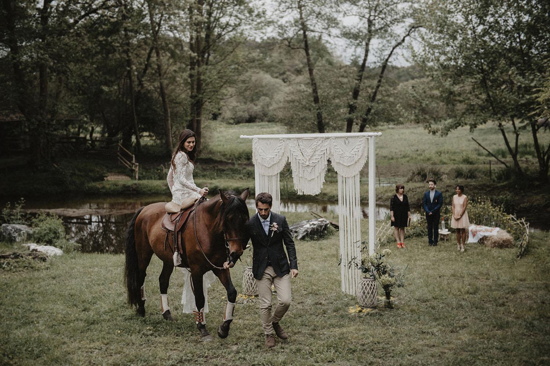 Cérémonie laïque sous les arbres au Coco Barn à Angresse, près de Hossegor. Photographe mariage moderne, reportage photo lifestyle. La mariée en robe Angeola mariage Biarritz à cheval. Grande arche en macramé.