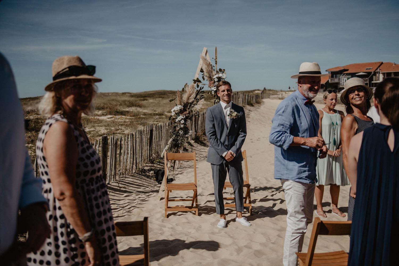 Cérémonie laïque en extérieur, dans les dunes, au bord de l'Océan dans les Landes, arrivée de la mariée en robe Pronovias, costume Hugo Boss, photographe mariage Pau