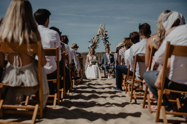 Photographe mariage Aquitaine, Pau, Hossegor, Biarritz. Cérémonie laïque au bord de l'Océan, les pieds dans le sable. Arche géométrique fleurie, l'herbe de la Pampa, eucalyptus.