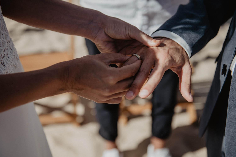 Echange d'alliances pendant la cérémonie laïque sur la plage. Photographe professionnel, reportage lifestyle, spontané. Pau, Bordeaux, Hossegor.