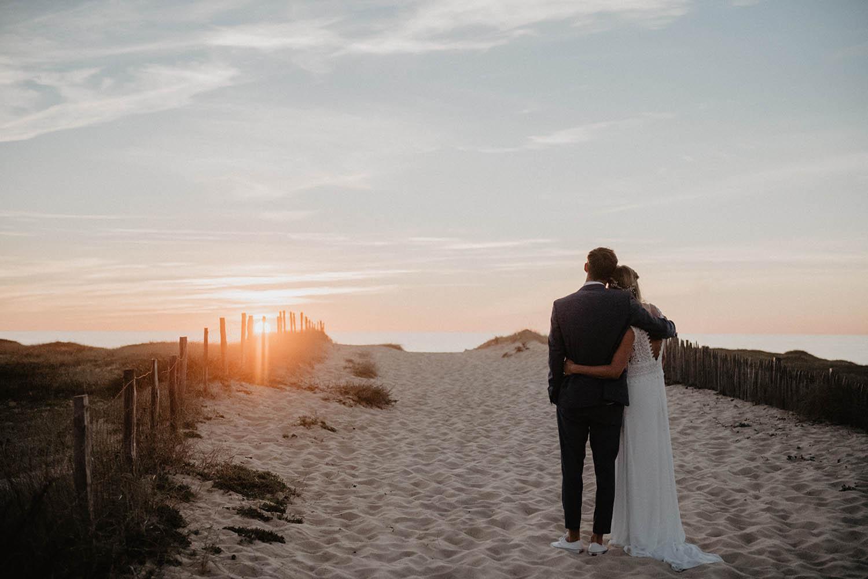 Robe de mariée dos nus en dentelle vintage. Séance photo de couple à l'Océan. Photographe Pau, Aquitaine. 64 Couple au coucher de soleil dans les dunes.