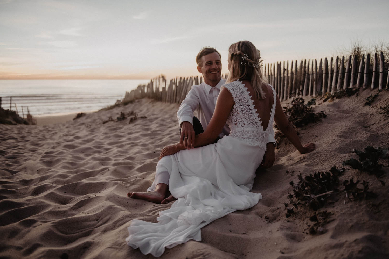 Couple au coucher d soleil dans les dunes, séance photo mariage sur la plage. Landes. Photographe lifestyle. Mariage folk.