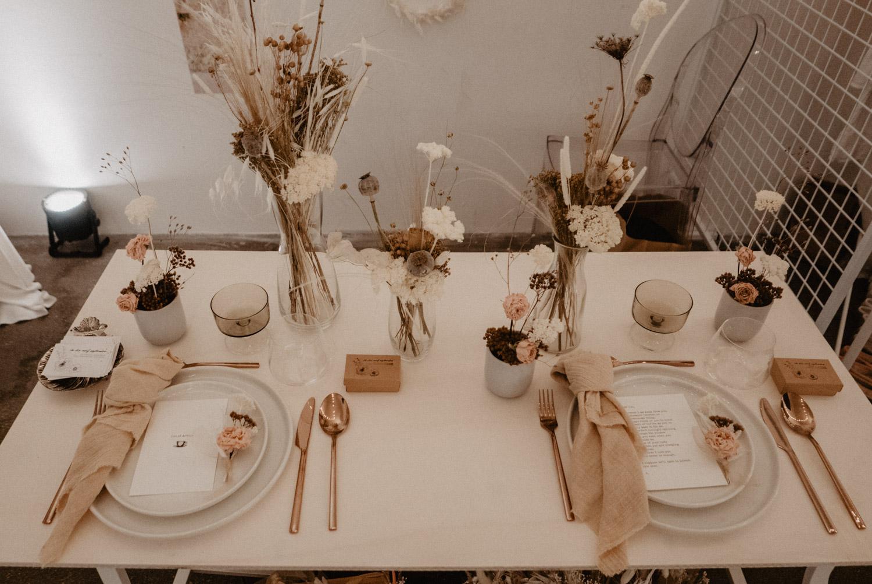 Photographe professionnel de mariage Pau en Aquitaine 64 Pyrénées Atlantiques. Déco de table de mariage en bois brute avec nappe naturelle couleur nude pour un mariage bohème et authentique.