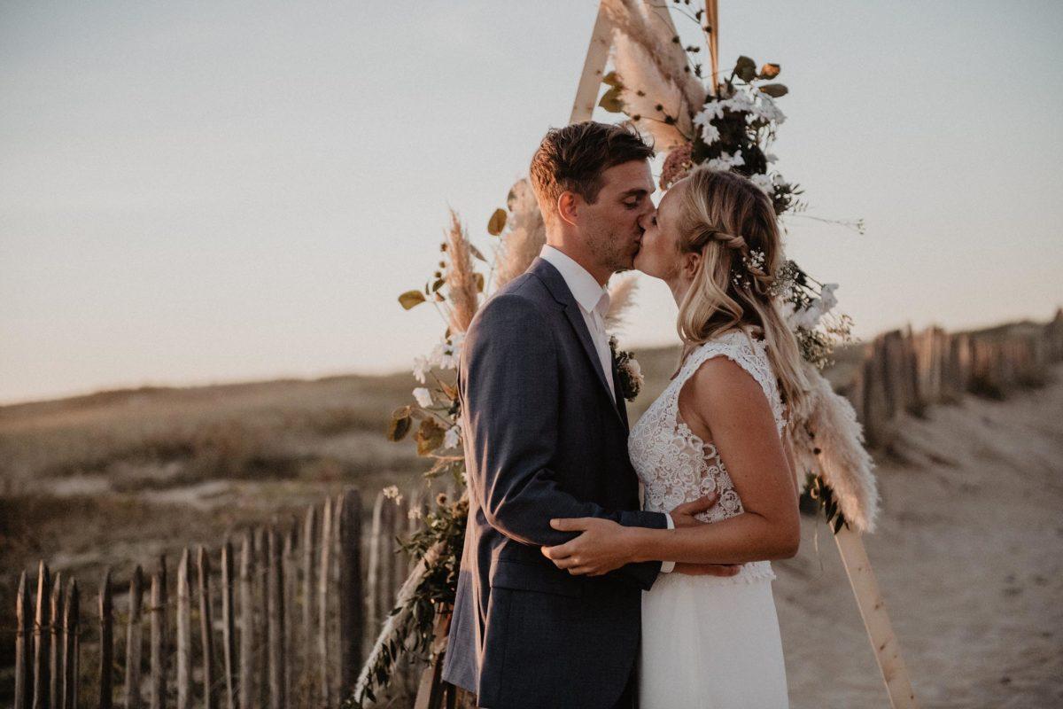 photographe mariage, arche géométrique et végétale pour cérémonie laïque bohème sur la plage, Landes, robe de mariée Pronovias, costume du marié Hugo Boss