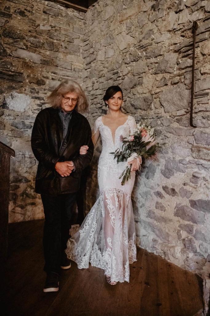 La mariée arrive à la Cérémonie laïque dans une Salle de réception atypique, verrière ancienne, mariage sous la pluie, Domaine de Lucain, 64, Pau, Aquitaine, robe romantique brodée de perles, Angeola mariage Biarritz