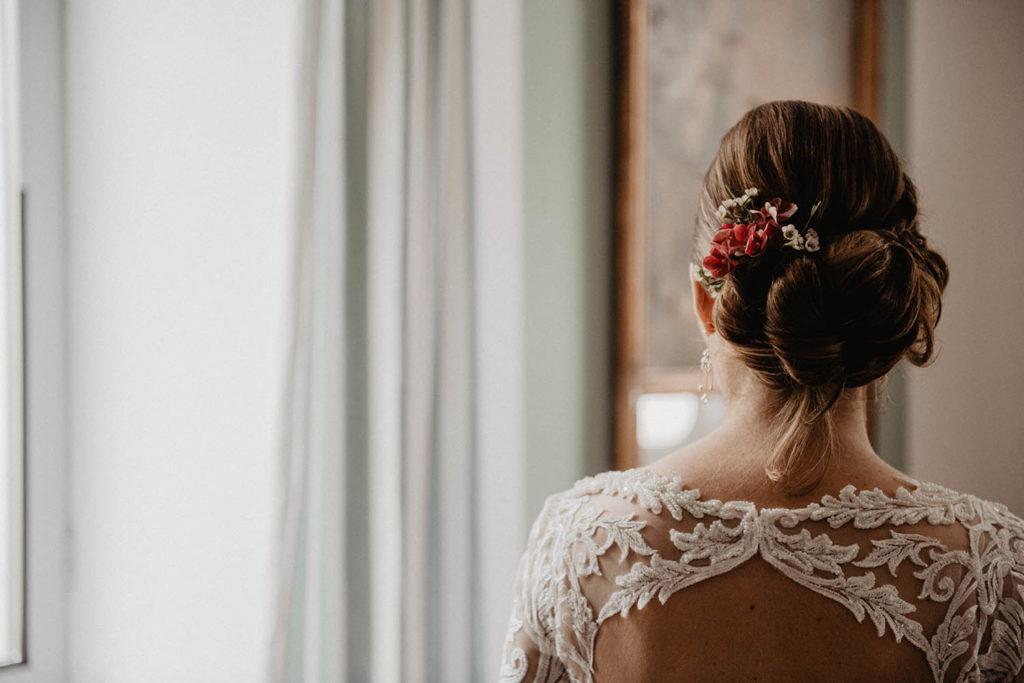 Détail du dos de la mariée, fleurs dans le chignon, robe dos nus brodée de perles Angeola mariage Biarritz, Domaine de Lucain, salle ed réception authentique près de Pau, 64