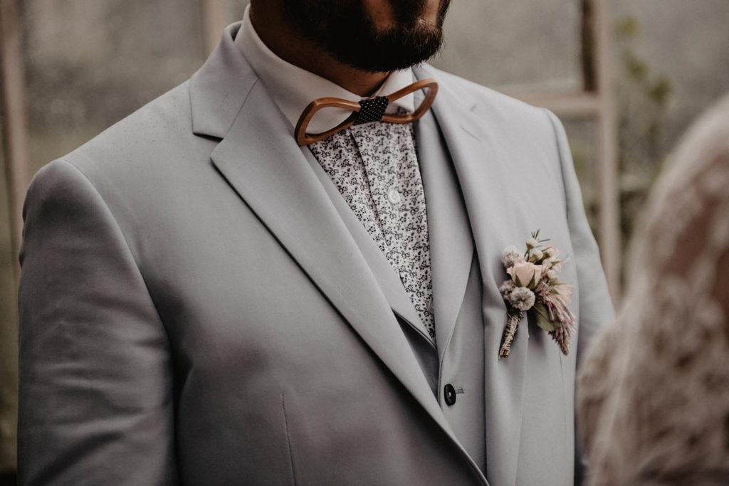 Détail du costume de marié bleu clair, chemise à fleurs, noeud pas en bois, boutonnière romantique, Serrada couture Biarritz