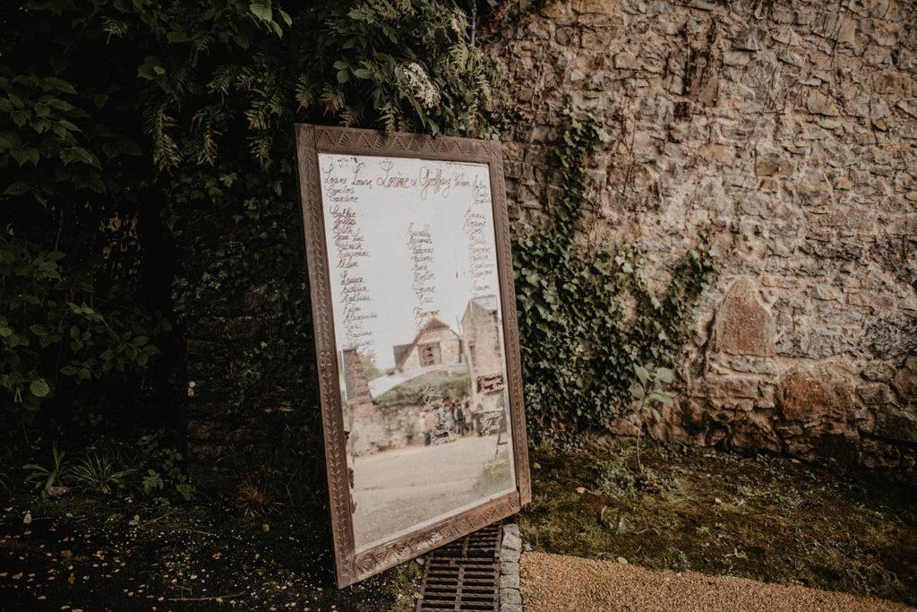 Plan de table de mariage original sur un miroir ancien devant la salle de réception au Domaine de Lucain, près de Pau