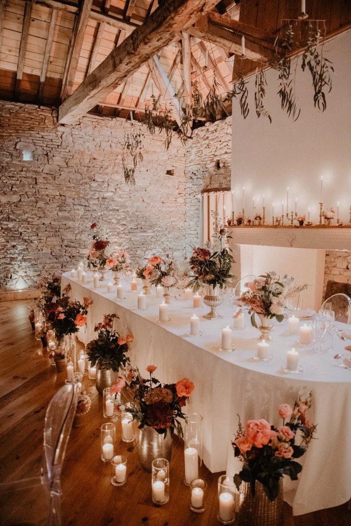 Mariage romantique au Domaine de Lucain sur les coteaux de Jurançon, table de mariés fleurie avec beaucoup de bougies